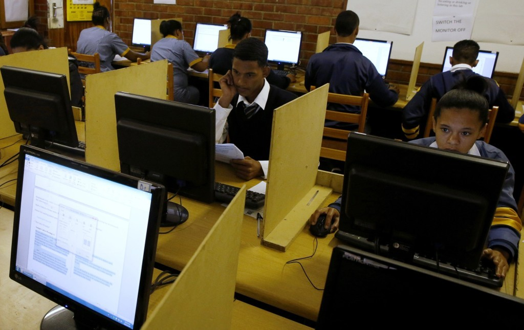 Students use computers to study at Elswood Secondary School in Cape Town November 7, 2013. Even the metal grills welded into its walls did not deter burglars from ripping out the copper cables that delivered Internet to the students of this tough neighbourhood. But Elswood's pupils were saved by alternative technology - free wireless connection via unused TV spectrum known as white space. It's being provided by a consortium including Google as part of a wider trial. Elsewhere in the country Microsoft is operating similar pilots. Both are racing to fine tune a technology that could ultimately bring cheap broadband to the entire continent. Picture taken November 7, 2013. To match Feature AFRICA-INTERNET/ REUTERS/Mike Hutchings (SOUTH AFRICA - Tags: EDUCATION BUSINESS SCIENCE TECHNOLOGY)